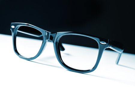 shortsightedness: a pair of black plastic-rimmed eyeglasses on a white surface, and a black background