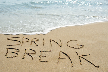 the text spring break written in the sand of a beach