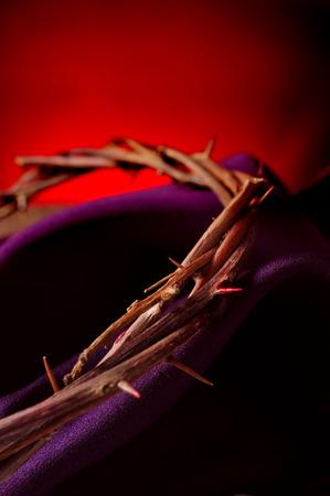 primer plano de la corona de espinas de Jesucristo en una tela de color púrpura Foto de archivo