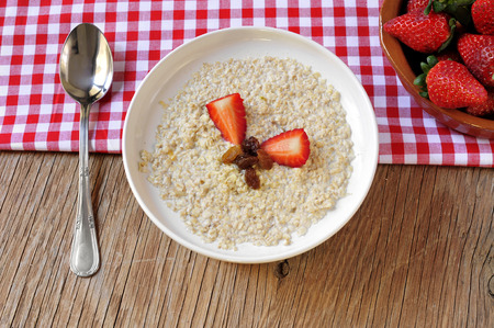 millet: high-angle shot of a bowl with porridge with sultana raisins and pieces of strawberry, on a rustic wooden table set for breakfast with a red and white checkered tablecloth and a bowl with strawberries