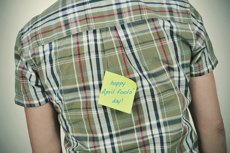 a young caucasian man wearing a plaid patterned shirt with a yellow sticky note attached to his back with the text happy april fools day written in it Stock Photo