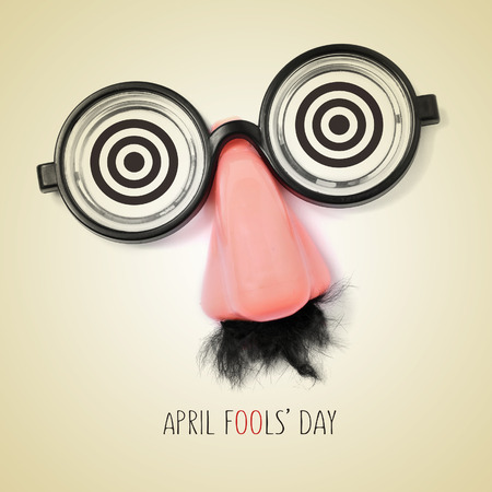 fake eyeglasses, nose and mustache and the sentence april fools day written in a beige background, with a retro effect 스톡 콘텐츠