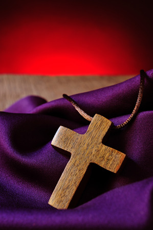 christian symbol: a simple wooden Christian cross on a purple drapery Stock Photo