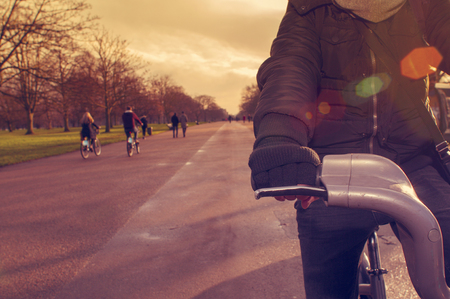 sheltered: closeup of a young caucasian man very sheltered riding a bicycle in Hyde Park in winter in London, United Kingdom, filtered and with a lens flare