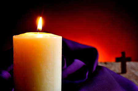 martyrdom: closeup of a lit candle with a purple drapery in the background and a Christian cross, on a wooden rustic surface and a red lighted background