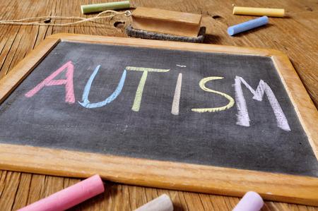 le mot autisme écrite à la craie de différentes couleurs dans un tableau placé sur un bureau ou une table en bois rustique