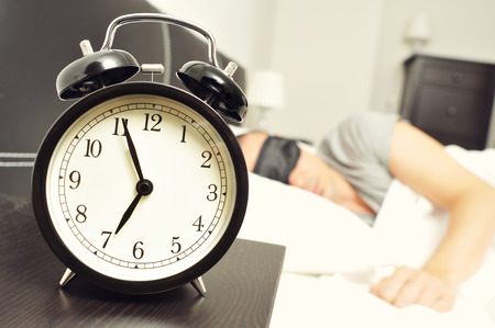 night table: closeup of an alarm clock at 6.55 in the morning on the night table and a young caucasian man sleeping in bed with a black sleep mask Stock Photo