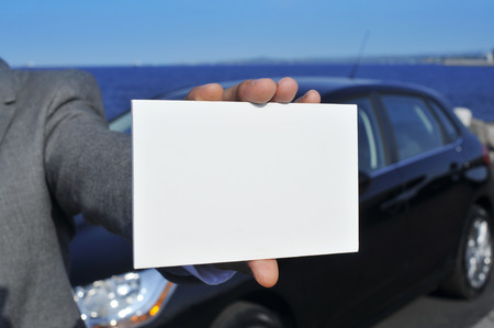 car retailer: closeup of a young caucasian man in a grey suit showing a blank signboard with a black car in the background Stock Photo
