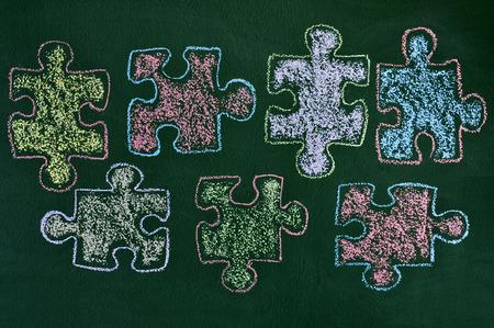 quelques pièces de puzzle tirés avec de la craie de couleurs différentes sur un tableau vert, comme le symbole de la sensibilisation à l'autisme