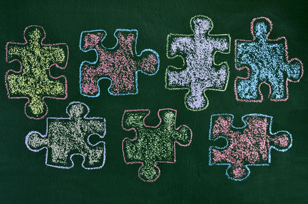 developmental disorder: some puzzle pieces drawn with chalk of different colors on a green chalkboard, as the symbol for the autism awareness