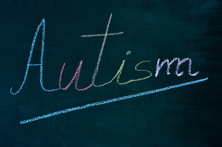 developmental disorder: the word autism with its letters written with chalk of different colors on a green chalkboard