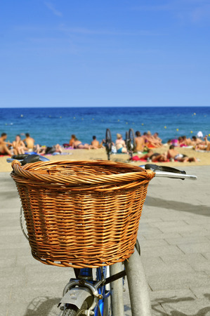 basket: closeup of a bicycle with a wicker basket parked in the seafront with blurred people on the beach in the background Stock Photo