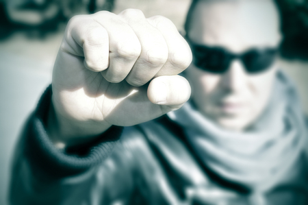 anarchism: closeup of a young man in a protest raising his fist and with his face blurred, with a filter effect Stock Photo
