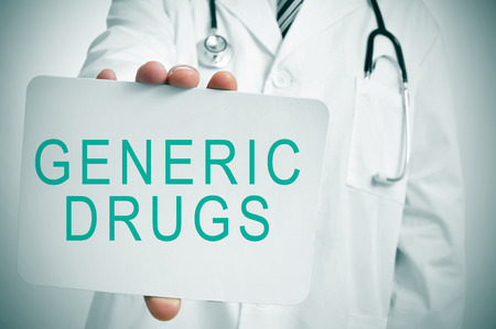 generic drugs: closeup of a young caucasian doctor showing a signboard with the text generic drugs written in it