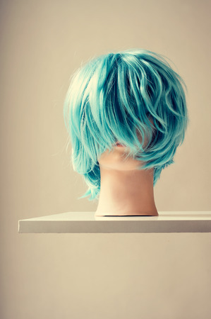 mannequin head: a blue wig in a mannequin head on a white shelf mounted on the wall Stock Photo