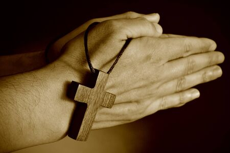 holy week: closeup of a young man praying with a wooden cross in his hands, in sepia toning