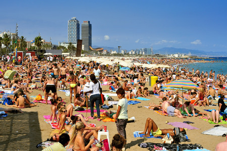 spain: Barcelona, Spain - August 19, 2014: A crowd of bathers in La Barceloneta Beach in Barcelona, Spain. This popular beach hosts about 500000 visitors from everywhere during the summer season Editorial