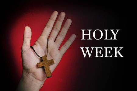 holy thursday: closeup of a wooden cross in the hand of a young caucasian man and the text holy week written in white on a red and black background