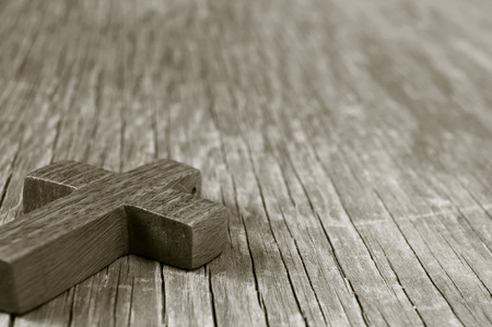 spiritualism: closeup of a wooden Christian cross on a rustic wooden surface, in sepia toning