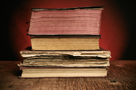 erudition: a pile of worn-out old books on a rustic wooden table