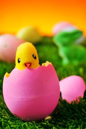 huevos de pascua: una chica de peluche que emerge de un huevo rosado de Pascua en la hierba y una Pascua conejo verde y un mont�n de huevos de colores decorados en el fondo