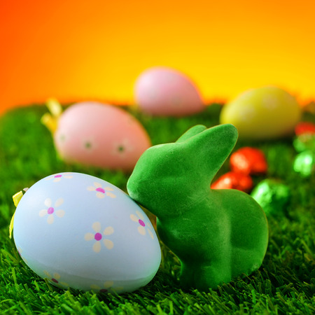 decorated eggs: closeup of a green easter rabbit and a blue flower-patterned easter eggs on the grass with some colorful decorated eggs in the background Stock Photo