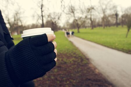 sheltered: closeup of a young caucasian man very sheltered wearing fingerless gloves holds a hot drink in a paper cup in Hyde Park in winter in London, United Kingdom Stock Photo