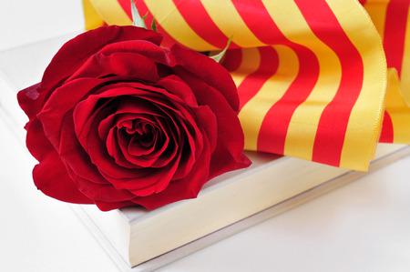 una rosa roja y la bandera catalán en un libro para Sant Jordi Foto de archivo