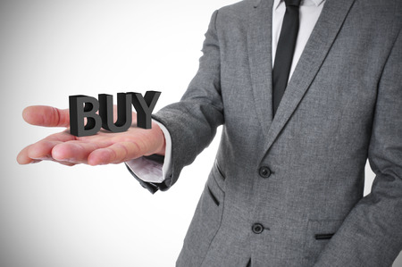 consumerist: a young businessman wearing a gray suit shows the word buy, three-dimensional, in the palm of his hand Stock Photo