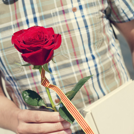sant: a young man with a red rose and the catalan flag, and a book for Sant Jordi, the Saint Georges Day, when it is tradition to give red roses and books in Catalonia, Spain Stock Photo