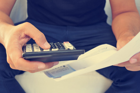 budget crisis: closeup of a young man checking a bill, a budget or a payroll with a calculator, filtered effect