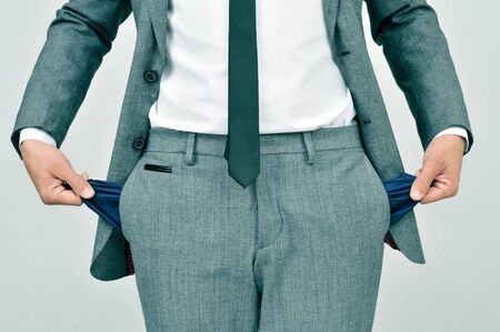 impoverish: broke businessman wearing a gray suit showing his empty pockets