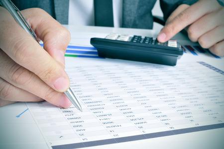 Zbliżenie młodego biznesmena sprawdzania rachunków z kalkulatora w jego biurze