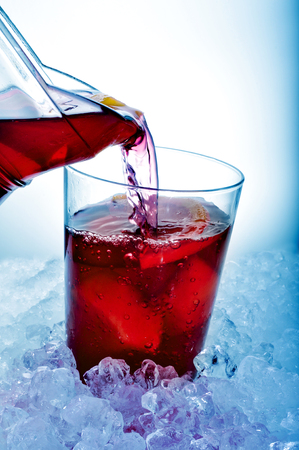 thirstiness: closeup of a glass with typical spanish sangria being filled from a pitcher