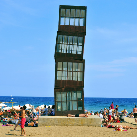 vacationers: Barcelona, Spain - August 19, 2014: Vacationers in the Barceloneta Beach in Barcelona, Spain. A sculpture designed by artist Rebecca Horn in COR-TEN steel presides over this urban beach Editorial