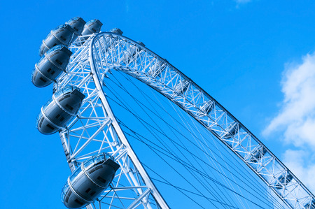 eye traveller: London, United Kingdom - January 19, 2015: Detail of the London Eye against the blue sky in London, United Kingdom. It is the tallest Ferris wheel in Europe with 135 meters high