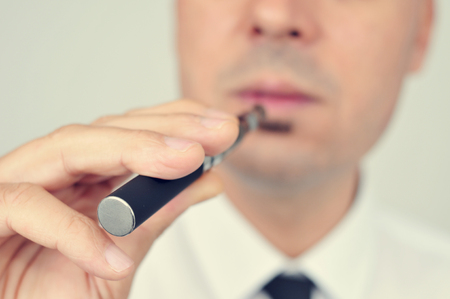 safer: closeup of a young caucasian man wearing a white shirt and black tie vaping with an electronic cigarette