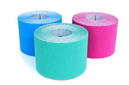elastic: some rolls of elastic therapeutic tape of different colors, pink and two different shades of blue, on a white background