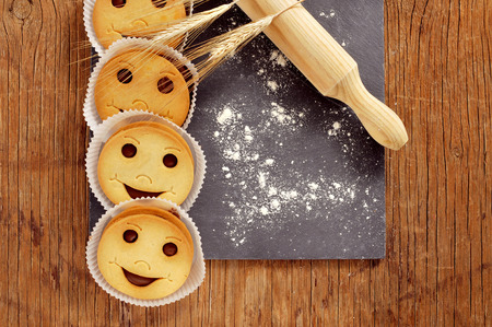 breakfast smiley face: high-angle shot of some smiley biscuits, some ears of wheat, a wooden rolling pin, and wheat flour sprinkled in a black slate plate placed on a wooden rustic table Stock Photo