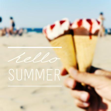 de tekst hello zomer op een wazig beeld van een aantal ijsjes in de hand van een jonge man op het strand