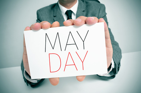 joblessness: a young caucasian man wearing a gray suit shows a signboard with the text may day written in it