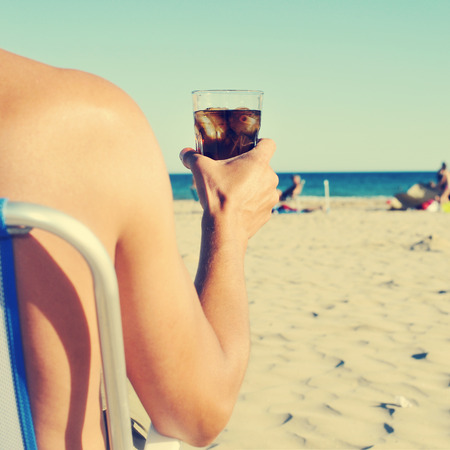 a young caucasian man hanging out on the beach with a glass with cola drink, with a filter effect
