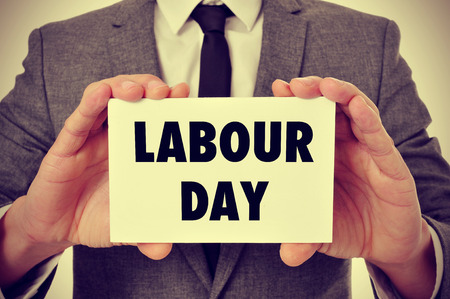 labor: a young caucasian man wearing a gray suit shows a signboard with the text labour day written in it, filtered Stock Photo