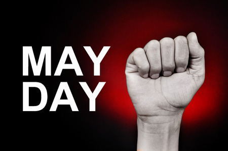 joblessness: closeup of the raised fist of a young caucasian man and the text may day on a red background Stock Photo