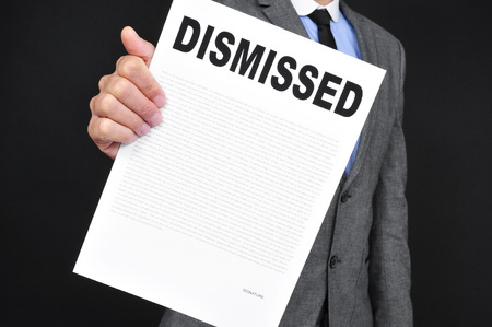 unemployed dismissed: a young caucasian man in gray suit showing a document with the text dismissal written in it on a black background