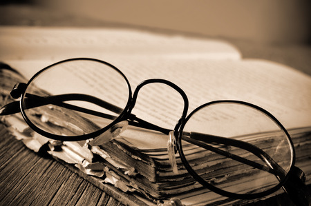 historic world event: a pair of round-framed eyeglasses on an old book, on a rustic wooden table, in sepia toning and slight vignette added Stock Photo