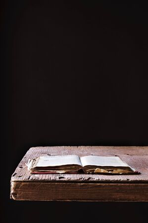 prose: an open old book on a rustic wooden table, on a black background