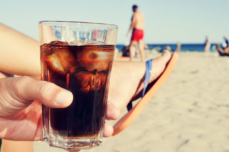 thirsting: Closeup of a young caucasian man hanging out on the beach with a glass with cola drink