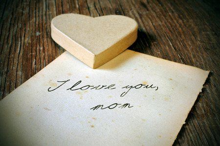tex: a cardboard heart and and old sheet of paper with the tex I love you, mom written in it on a rustic wooden table, with a retro effect and a slight vignette added