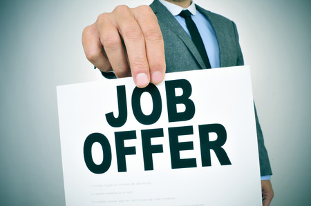 close-up van een jonge zakenman in een grijs pak toont een bord met de tekst jobaanbieding geschreven in het